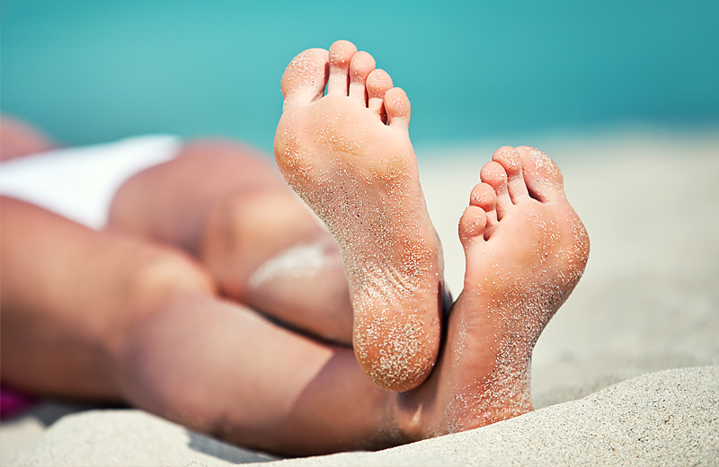 A colour image of the tanned legs and feet of a person lying on a beach after receiving spray tanning by Vicki Hooper Beauty - Grayshott & Headley Down